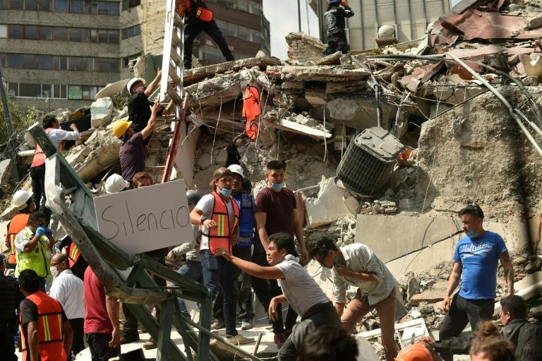 """A placard reads """"Silence"""" as rescuers hurry to free possible victims out of the rubble of a collapsed building in Mexico City"""