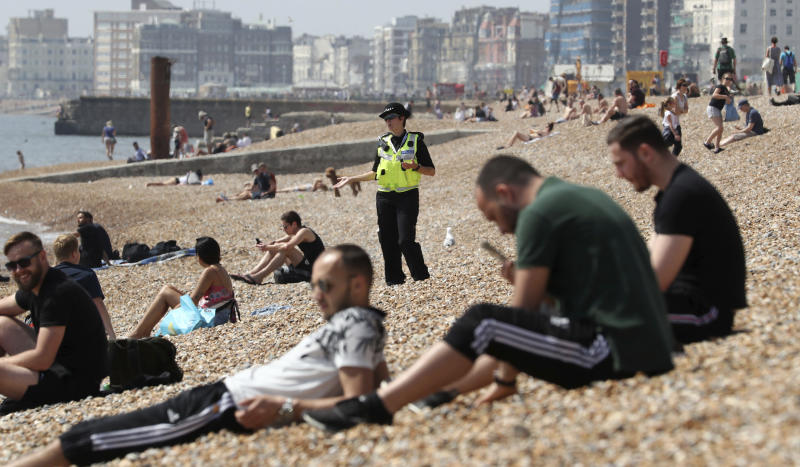 A police officer advises a group of people to move from Brighton Beach in East Sussex, England as the UK continues in lockdown to help curb the spread of the coronavirus, Saturday May 9, 2020. (Gareth Fuller/PA via AP)