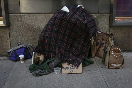 A homeless couple huddle together on 42nd Street in the Manhattan borough of New York, January 4, 2016. REUTERS/Carlo Allegri
