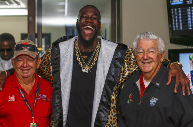 WBC Heavyweight Champion Deontay Wilder, center, poses with Donnie Allison, left, and Bobby Allison before the GEICO 500 NASCAR Talladega auto race at Talladega Superspeedway, Sunday, April 29, 2018, in Talladega, Ala. (AP Photo/Butch Dill)