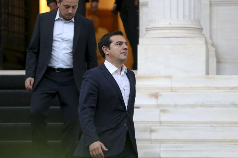 Greek PM Tsipras is followed by Minister of State Pappas and government spokesman Sakelaridis as he leaves his office to visit Greek President Prokopis Pavlopoulos in Athens