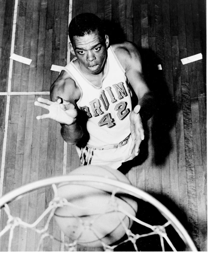 FILE - In this 1962 file photo, UCLA basketball guard Walt Hazzard, poses under a net.  Hazzard, the former UCLA and NBA star who played on the Bruins' first NCAA championship basketball team in 1964 and later coached the team for four seasons in the 1980s, has died. He was 69. The school says Hazzard died Friday, Nov. 18, 2011, at UCLA Ronald Reagan Medical Center after a long illness. (AP Photo, File)