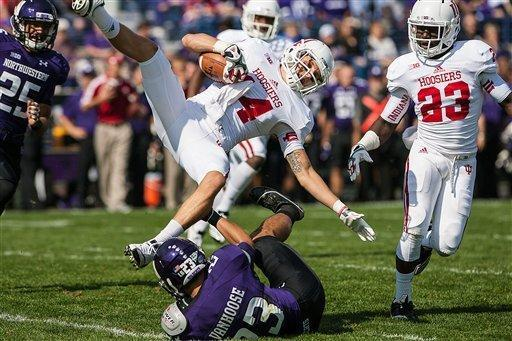 Indiana's Nick Stoner, top, is tackled by Northwestern's Nick VanHoose (23) on a punt return in the first quarter of an NCAA college football game in Evanston, Ill. on Saturday, Sept. 29, 2012. (AP Photo/Charles Cherney)
