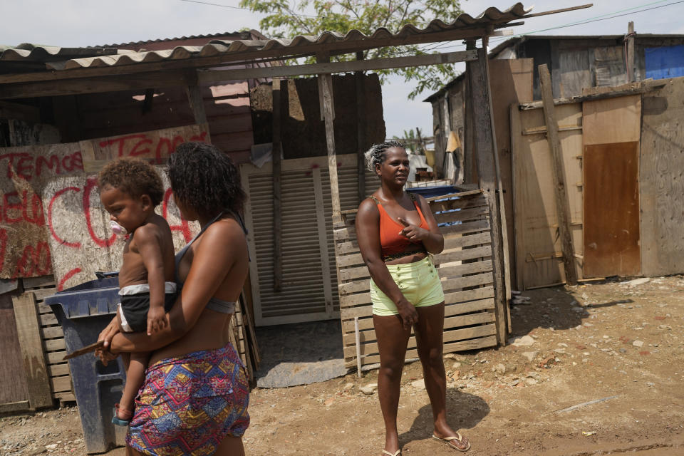 Francielle de Santana, right, stands outside her home in the Jardim Gramacho favela of Rio de Janeiro, Brazil, Monday, Oct. 4, 2021. Due to the rise in gas prices, Santana says she'll have to go around scraping for any recyclable material to sell to be able to afford to buy a new gas cylinder to cook. (AP Photo/Silvia Izquierdo)