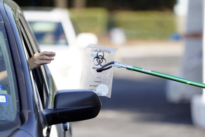 A sample is collected at a Texas Division of Emergency Management free COVID-19 testing site at Minute Maid Park Saturday, Aug. 8, 2020, in Houston. The newly opened mega site, which has eight drive-thru lanes and four walk-up lanes, has the ability to process 2,000 tests per day. (AP Photo/David J. Phillip)