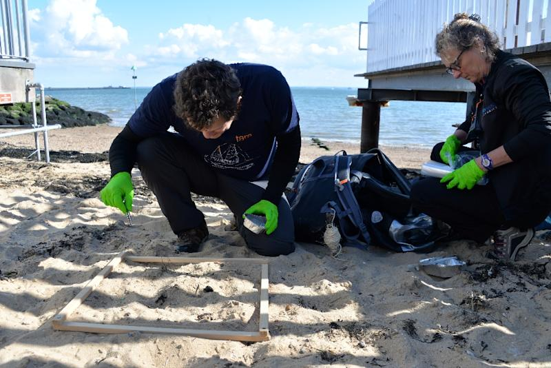 Researchers Valerie Barbe (R) and Boris Eyheraguibel, members of Tara's microplastics expedition, look for plastics in the sand on Southend-at-sea beach near London (AFP Photo/Amélie BOTTOLLIER-DEPOIS)