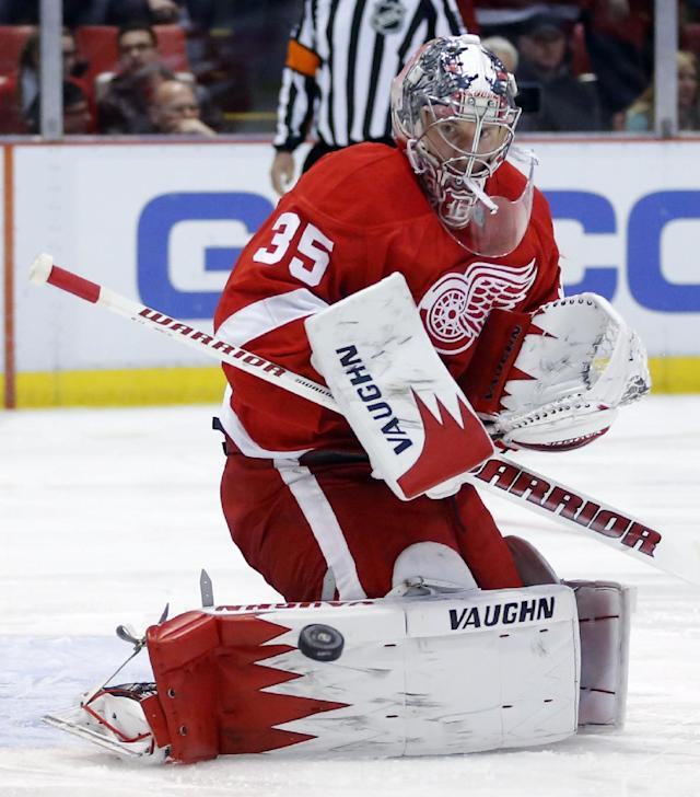 Detroit Red Wings goalie Jimmy Howard (35) deflects a shot from the Edmonton Oilers during the first period of an NHL hockey game Friday, March 14, 2014, in Detroit. (AP Photo/Duane Burleson)