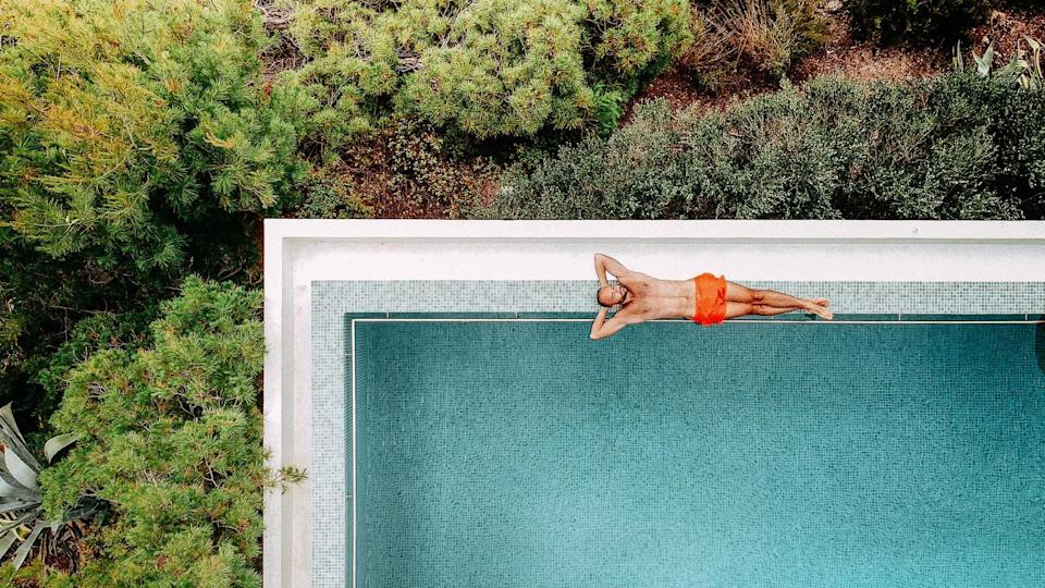 Aerial view of a young man relaxing by the infinity pool.