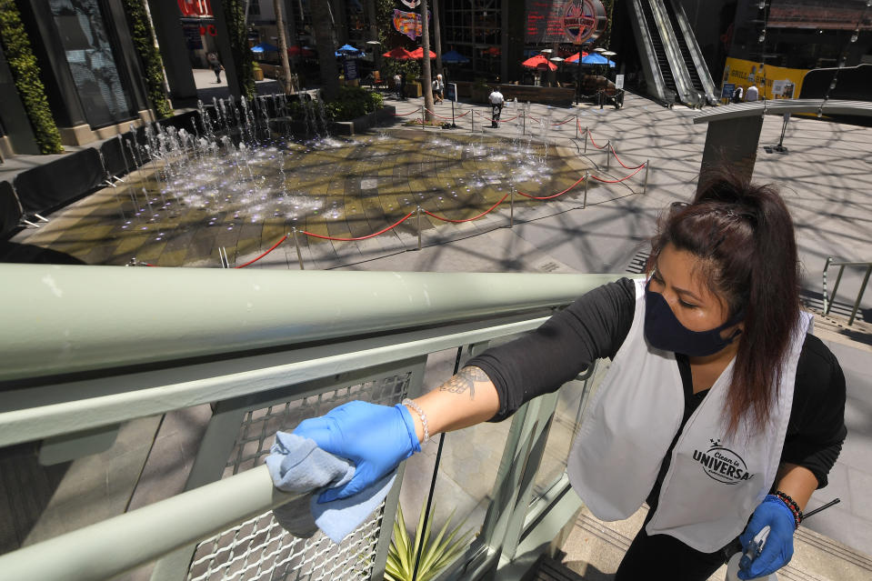 Andrea Castaneda cleans the railings at Universal CityWalk, Thursday, June 11, 2020, near Universal City, Calif. The tourist attraction, which had been closed due to the coronavirus outbreak recently re-opened. The Universal Studios tour is still closed. (AP Photo/Mark J. Terrill)