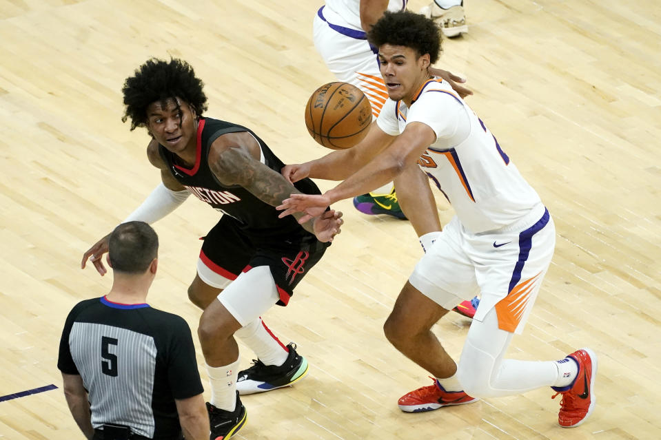 Houston Rockets guard Kevin Porter Jr. and Phoenix Suns forward Cameron Johnson, right, battle for a loose ball during the first half of an NBA basketball game, Monday, April 12, 2021, in Phoenix. (AP Photo/Matt York)