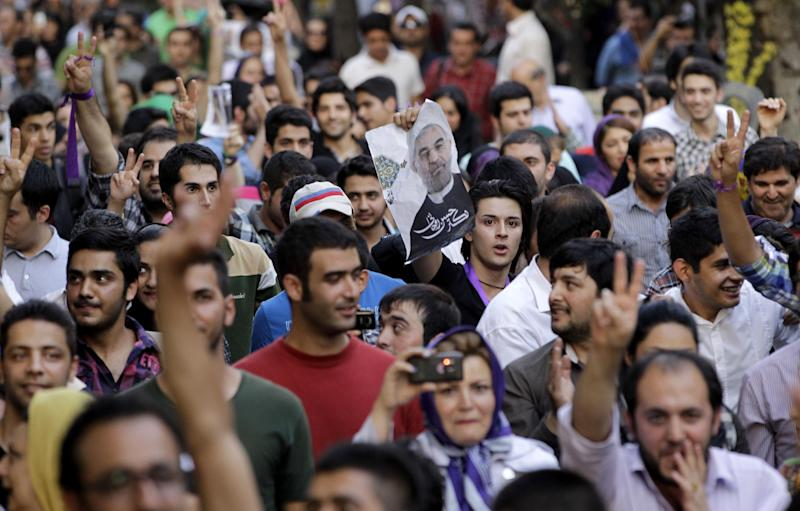 Supporters of the Iranian presidential candidate Hasan Rowhani, shown in poster at center, attend a celebration gathering in Tehran, Iran, Saturday, June 15, 2013. Moderate cleric Hasan Rowhani was declared the winner of Iran's presidential vote on Saturday after gaining support among many reform-minded Iranians looking to claw back a bit of ground after years of crackdowns. (AP Photo/Vahid Salemi)