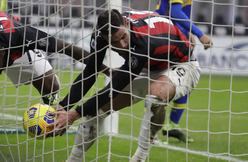 AC Milan's Theo Hernandez holds the ball after scoring his side's first goal during a Serie A soccer match between AC Milan and Parma, at the San Siro stadium in Milan, Italy, Sunday, Dec. 13, 2020. (AP Photo/Luca Bruno)