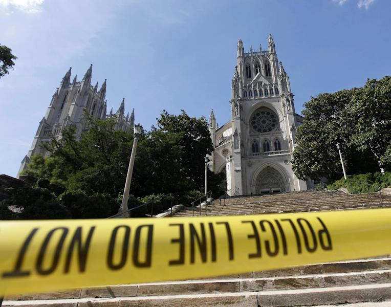 FILE - In this Aug. 23, 20111 file photo, police tape is seen in front of the National Cathedral in the Washington after an earthquake hit the Washington area. An earthquake last August severely damaged its intricate stone work and architecture with repairs now estimated to cost $20 million. Even before the earthquake, though, a financial crisis forced the cathedral to slash its budget from $27 million to $13 million in recent years and cut its paid staff by more than half from 170 full-time employees to 70. (AP Photo/Pablo Martinez Monsivais, File)