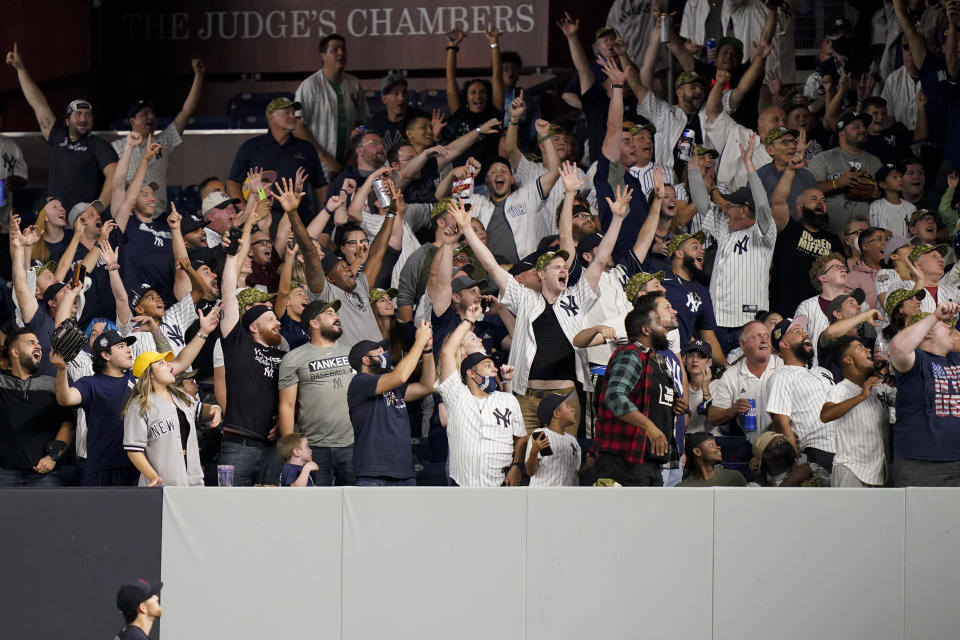 Fans celebrate after New York Yankees' Brett Gardner hit a three-run home run off Cleveland Indians relief pitcher Nick Wittgren during the seventh inning of a baseball game Friday, Sept. 17, 2021, in New York. (AP Photo/John Minchillo)