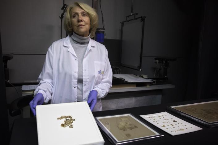 Israel Antiquities Authority conservator Tanya Bitler shows newly discovered Dead Sea Scroll fragments at the Dead Sea scrolls conservation lab in Jerusalem, Tuesday, March 16, 2021. Israeli archaeologists on Tuesday announced the discovery of dozens of new Dead Sea Scroll fragments bearing a biblical text found in a desert cave and believed hidden during a Jewish revolt against Rome nearly 1,900 years ago. (AP Photo/Sebastian Scheiner)