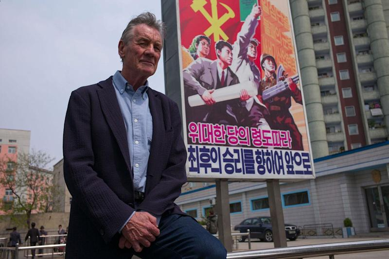 Wish you were here? Michael Palin beside a propaganda poster in the North Korean capital, Pyongyang: Channel 5