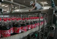 FILE PHOTO: An employee works at a production line at the Coca Cola plant in Nanjing