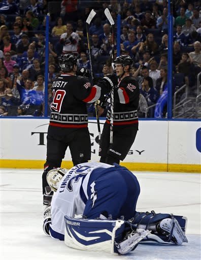 Carolina Hurricanes' Jiri Tlusty, left, celebrates his second goal of the first period with teammate Eric Staal in front of Tampa Bay Lightning goalie Anders Lindback, of Sweden, during an NHL hockey game, Sunday, April 21, 2013, in Tampa, Fla. (AP Photo/Mike Carlson)