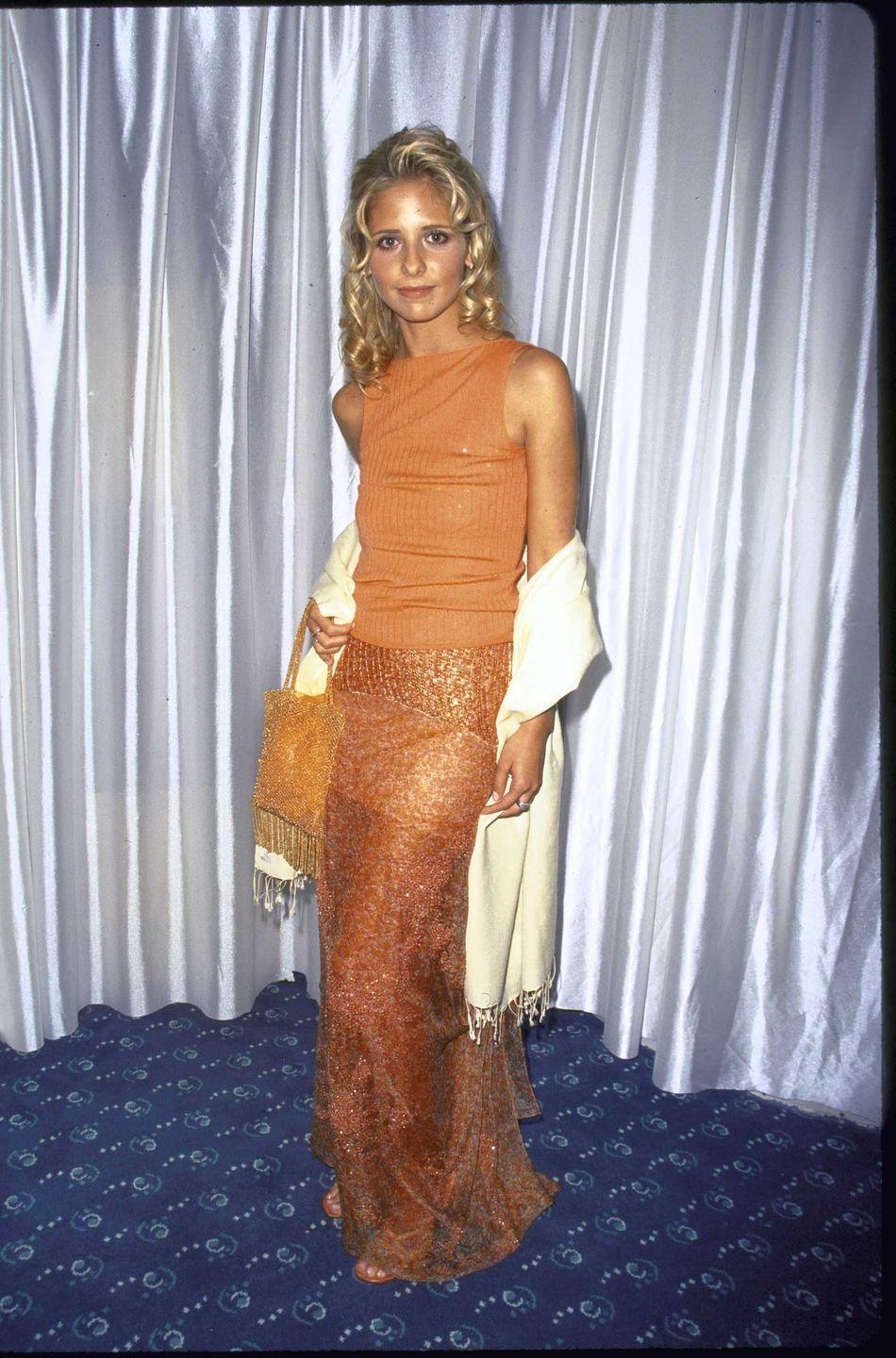 <p>A young Sarah Michelle Gellar exudes a '90s look in her orange ensemble, seen here in 1999 at a <em>Saturday Night Live</em> anniversary event. </p>