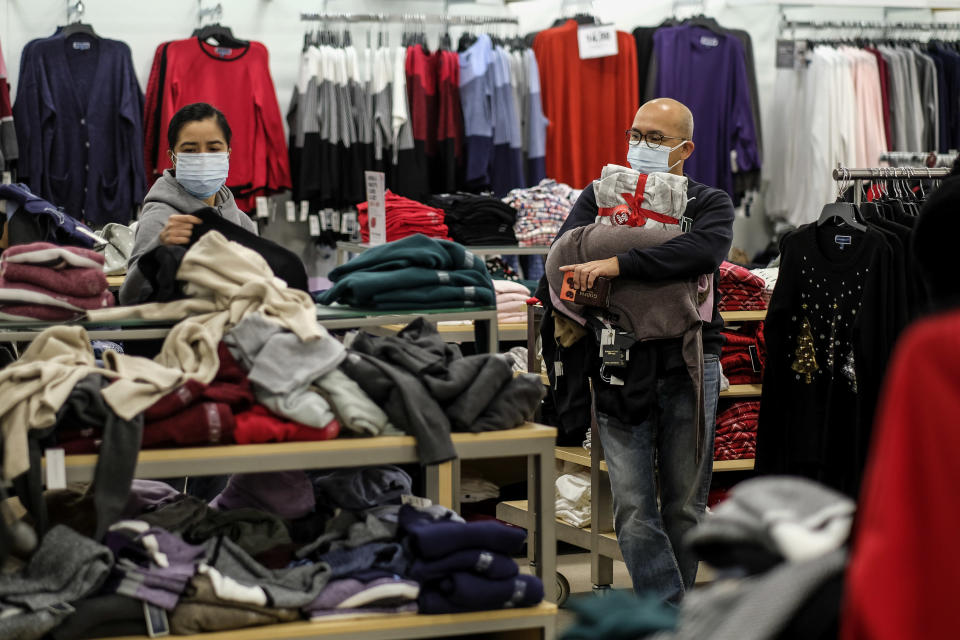 Black Friday shopper Alex Gamboa, right, 58, of Los Angeles, holds merchandises as his wife, who did not give her name, checks the bargains at the Glendale Galleria in Glendale, Calif., Friday, Nov. 27, 2020. (AP Photo/Ringo H.W. Chiu)