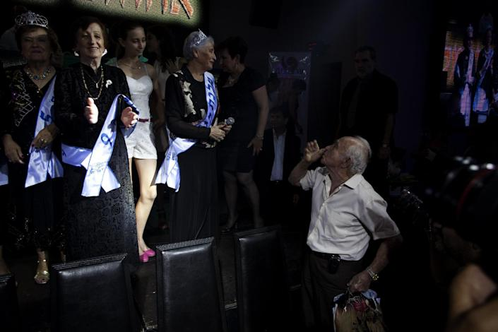 """An man sends a kiss to Holocaust survivors participating in a beauty pageant, in the northern Israeli city of Haifa, Thursday, June 28, 2012. Fourteen women who lived through the horrors of World War II paraded on stage Thursday night in an unusual pageant, vying for the honor of being Israel's first """"Miss Holocaust Survivor."""" (AP Photo/Sebastian Scheiner)"""
