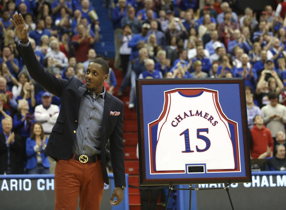 Former Kansas player and current Miami Heat member Mario Chalmers waves to the crowd as his college jersey is retired during a halftime ceremony at an NCAA college basketball game between Texas and Kansas, Saturday, Feb. 16, 2013, in Lawrence, Kan. (AP Photo/Ed Zurga)