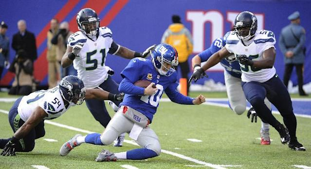 New York Giants quarterback Eli Manning (10) slides down to avoid being hit by Seattle Seahawks middle linebacker Bobby Wagner (54), outside linebacker Bruce Irvin (51) and defensive end Cliff Avril (56) during the first half of an NFL football game, Sunday, Dec. 15, 2013, in East Rutherford, N.J. (AP Photo/Bill Kostroun)