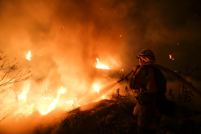 Firefighters battle flames on a hillside near homes in Santa Paula, California, as the Los Angeles region grapples with wind-whipped wildfires