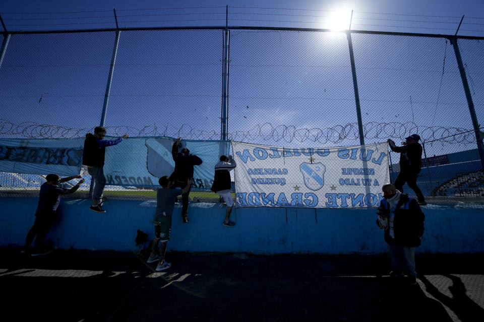 Temperley soccer fans hang banners before their team's match against Club Atletico Alvarado at the Alfredo Beranger Stadium, devoid of fans due to COVID-19 restrictions in Lomas de Zamora, Argentina, Friday, Aug. 27, 2021. Four hours before the match, soccer fans are allowed to enter and hang banners, and must remove them after the match. (AP Photo/Natacha Pisarenko)