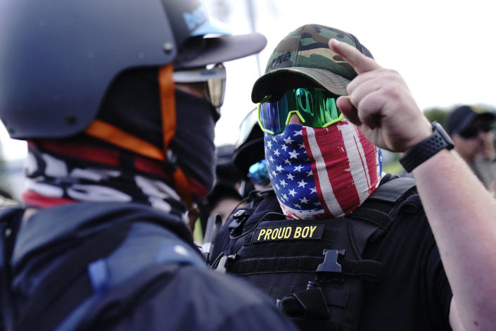 A right-wing demonstrator, right, gestures toward a counter protester as members of the Proud Boys and other right-wing demonstrators rally on Saturday, Sept. 26, 2020, in Portland, Ore.About 200 people gathered in Portland, for a right-wing rally, dozens of them wearing militarized body armor. It was far fewer than the thousands expected to appear. / Credit: John Locher / AP