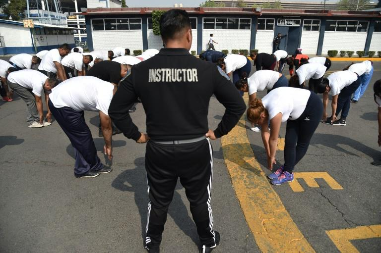 Physical trainer Javier Ramirez (C) works with police officers at a police unit in Mexico City