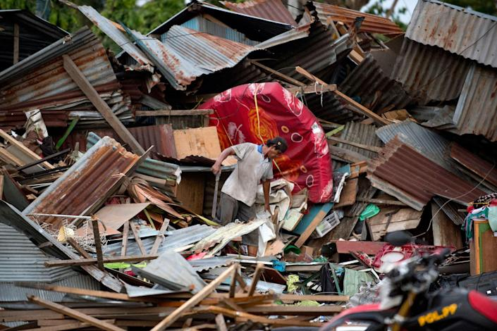 <p>A man looks for his belongings amid the debris of his destroyed house in Palu in Central Sulawesi on Sept. 29, 2018, after a strong earthquake and tsunami struck the area. (Photo: Bay Ismoyo/AFP/Getty Images) </p>