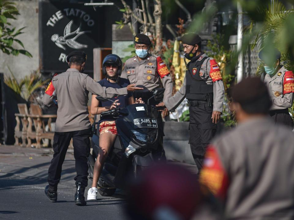 police in bali stop a man on a motorcycle not wearing a face mask