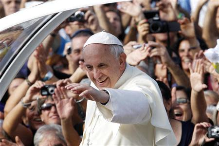 Pope Francis waves as he arrives to lead a mass outside the Shrine of Our Lady of Bonaria in Cagliari September 22, 2013. REUTERS/Giampiero Sposito