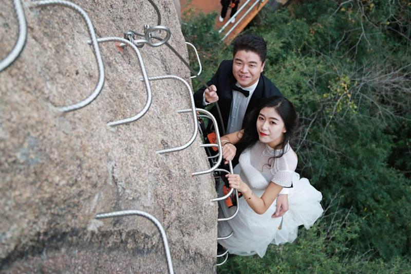 These incredible snaps show the bride and groom clinging to the side of the cliff, dressed-to-impress in their wedding gear. Photo: Australscope