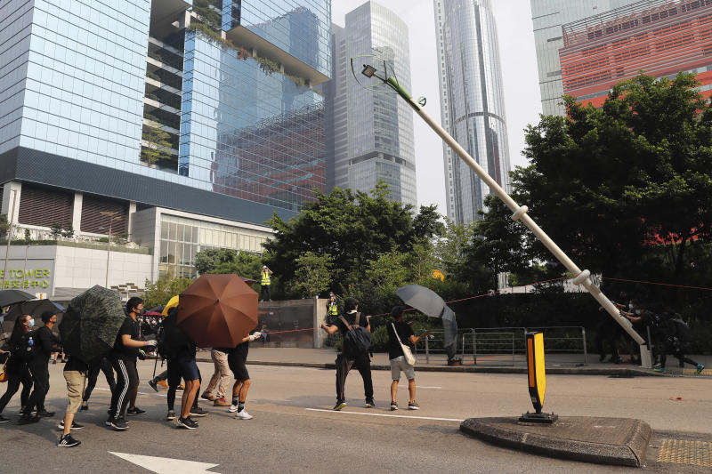 "Demonstrators try to pull down a smart lamppost during a protest in Hong Kong, Saturday, Aug. 24, 2019. Chinese police said Saturday they released an employee at the British Consulate in Hong Kong as the city's pro-democracy protesters took to the streets again, this time to call for the removal of ""smart lampposts"" that raised fears of stepped-up surveillance. (AP Photo/Kin Cheung)"