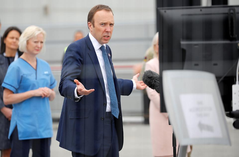 """Britain's Health Secretary Matt Hancock (C)speaks in front of a monitor during the opening of the """"NHS Nightingale"""" field hospital, created at the ExCeL London exhibition centre, in London on April 3, 2020, to help with the novel coronavirus COVID-19 pandemic. - The new state-run National Health Service (NHS) hospital, named after trailblazing 19th-century nurse Florence Nightingale, has been built in just nine days. (Photo by Tolga AKMEN / AFP) (Photo by TOLGA AKMEN/AFP via Getty Images)"""