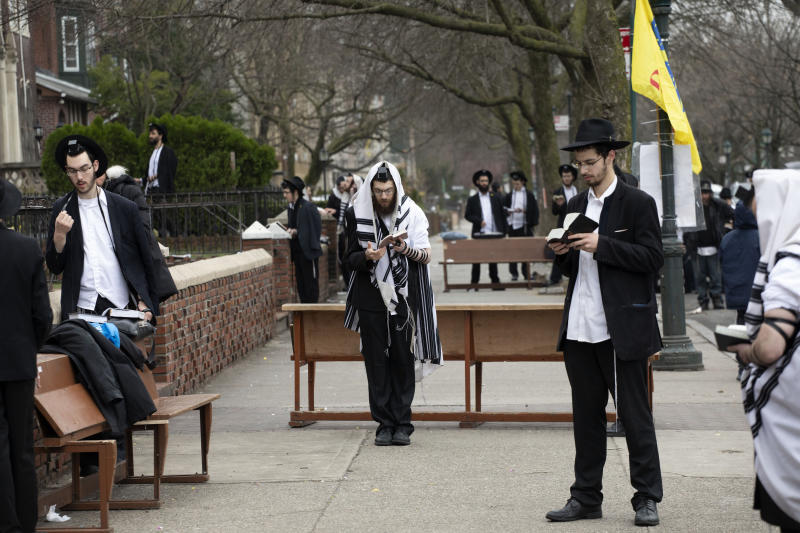 "Orthodox Jewish men use ""social distancing"" as they pray outside the Chabad Lubavitch World Headquarters, Friday, March 20, 2020 in the Brooklyn borough of New York, before leaders of six major organizations in their faith released a joint statement urging worshippers to ""avoid, to the maximum extent feasible, any outside interactions"" to help stop the coronavirus pandemic. Orthodox Jewish leaders mounted their show of unity to underscore to a wide swath of congregants the importance of behavioral changes that amount to a massive upheaval in their faith communities. (AP Photo/Mark Lennihan)"