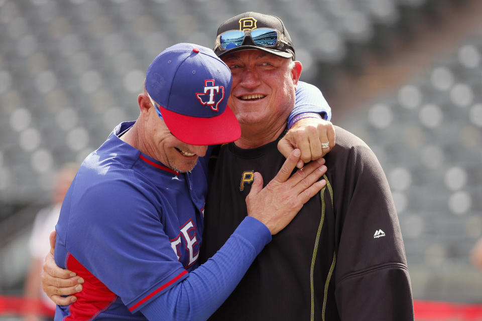 FILE - In this May 27, 2016, file photo, Texas Rangers manager Jeff Banister, left, and Pittsburgh Pirates manager Clint Hurdle greet each other during batting practice before a baseball game in Arlington, Texas. Hurdle began sending his daily notes of inspiration more than 10 years ago, during his days managing the Colorado Rockies. They were a simple, small way of checking in with everybody on his staff to discuss leadership ideas or offer support. (AP Photo/Tony Gutierrez, File)