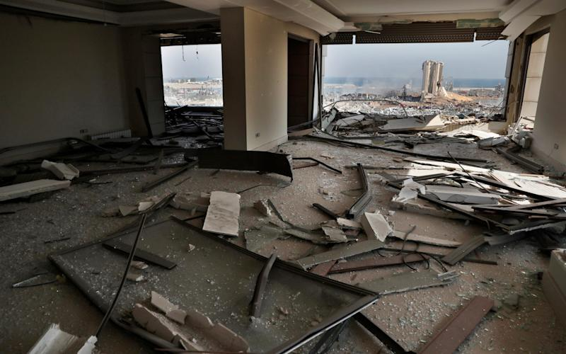 The scene of the explosion that hit the seaport of Beirut is seen through a damaged apartment in Beirut - AP