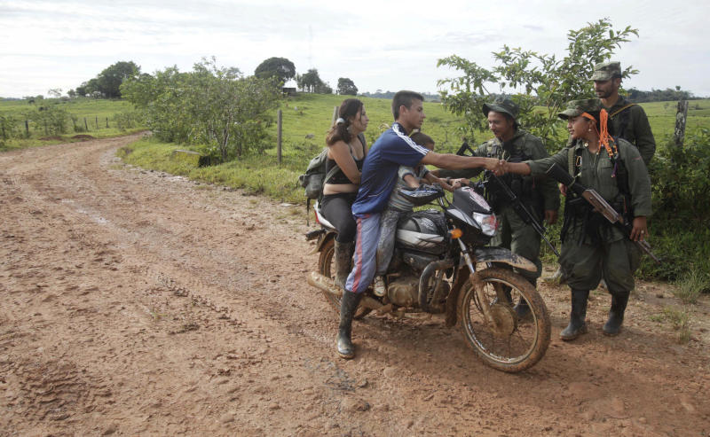 A man shakes hands with guerrillas of the Revolutionary Armed Forces of Colombia (FARC) who manage a roadblock in San Isidro in southern Colombia, Wednesday, May 30, 2012. Journalist Romeo Langlois, who was taken by rebels on April 28 when they attacked troops he was accompanying on a cocaine-lab eradication mission, is expected to be handed over by the rebels to a delegation that includes another French journalist in San Isidro. (AP Photo/Fernando Vergara)