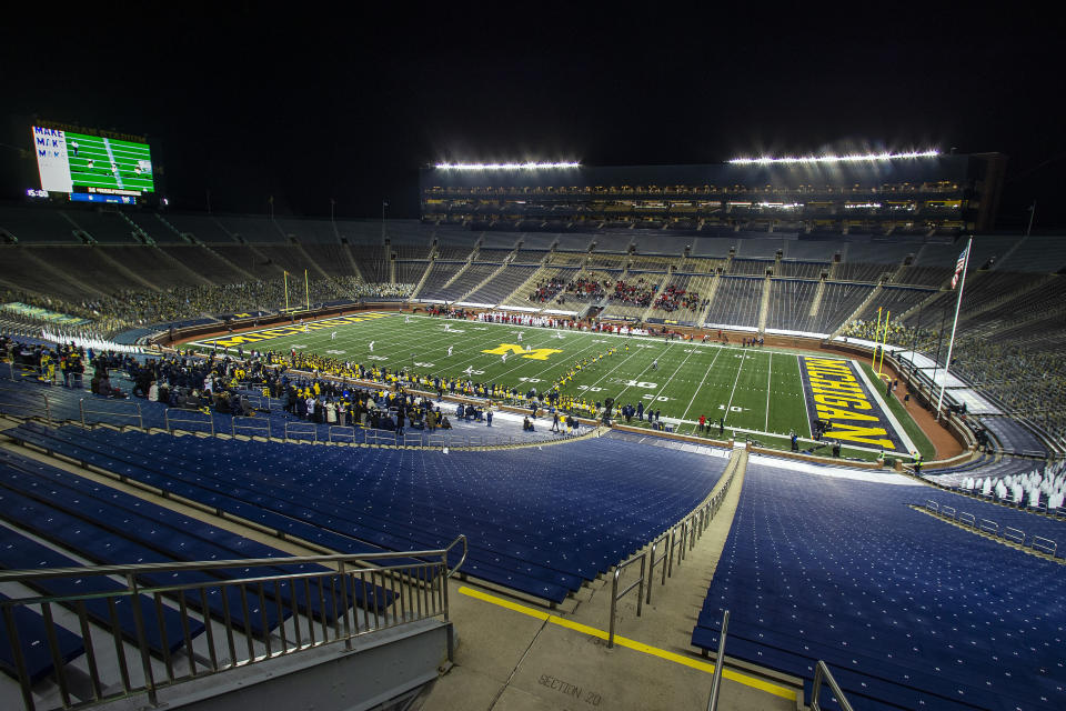A small number of athletes' invited guests from Michigan and Wisconsin watch in an otherwise empty Michigan Stadium at the kickoff of an NCAA college football game in Ann Arbor, Mich., Saturday, Nov. 14, 2020. (AP Photo/Tony Ding)