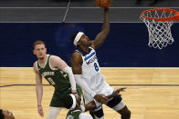 Minnesota Timberwolves' Jarred Vanderbilt (8) lays up a shot in front of Milwaukee Bucks' Donte DiVincenzo (0) in the first half of an NBA basketball game Wednesday, April 14, 2021, in Minneapolis. (AP Photo/Jim Mone)