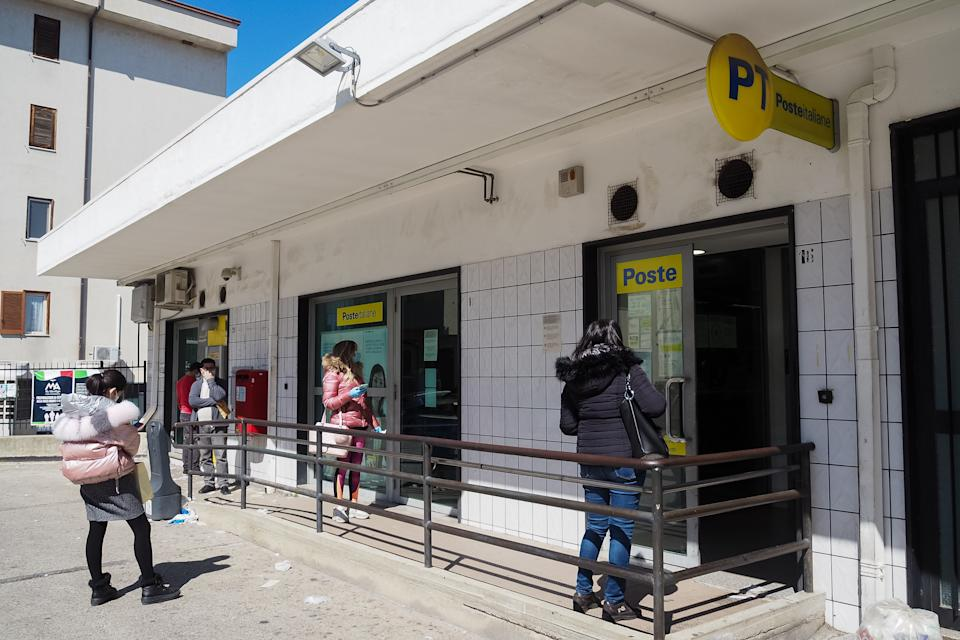 CORIGLIANO-ROSSANO, CALABRIA, ITALY - 2020/03/16: People keeping a safe distance queuing outside a post office wearing a mask for fear of Coronavirus infection (COVID-19). (Photo by Alfonso Di Vincenzo/KONTROLAB/LightRocket via Getty Images)