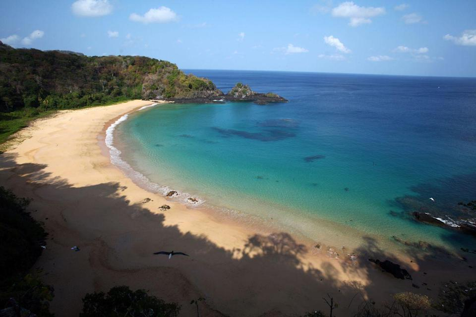 <p>Located 200 miles off Brazil's coast on Fernando de Noronha island, Baia do Sancho is only accessible via boat or by hiking down a narrow staircase from surrounding cliffs making it secluded and virtually untouched.</p>