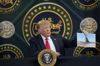 FILE - In this June 23, 2020 file photo, President Donald Trump holds an image of the U.S. border wall being built between the U.S. and Mexico as he participates in a border security briefing at United States Border Patrol Yuma Station in Yuma, Ariz. The Supreme Court is agreeing to review a Trump administration policy that makes asylum-seekers wait in Mexico for U.S. court hearings. As is typical, the court did not comment Monday in announcing it would hear the case. Because the court's calendar is already full through the end of the year, the justices will not hear the case until 2021. (AP Photo/Evan Vucci)
