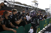 Mercedes driver Lewis Hamilton of Britain celebrates with his team after he clocked the fastest time during the qualifying session for the Hungarian Formula One Grand Prix, at the Hungaroring racetrack in Mogyorod, Hungary, Saturday, July 31, 2021. The Hungarian Formula One Grand Prix will be held on Sunday. (David W Cerny/Pool via AP)
