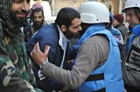 Members of a United Nations and Syria's Red Crescent convoy are welcomed by rebel fighters after entering a besieged district of Homs, on February 8, 2014