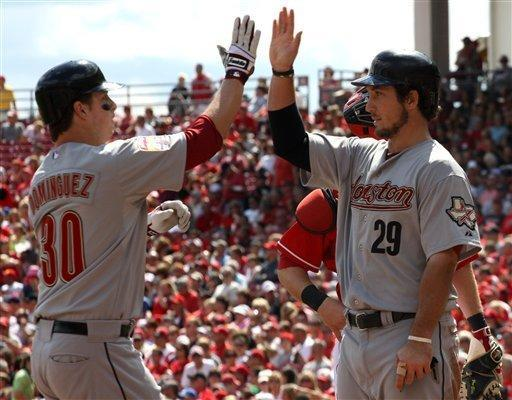 Houston Astros Matt Dominguez gets congratulated by Brett Wallace, right, after hitting a three-run home run off CIncinnati Reds Johnny Cueto in the third inning of their baseball game in Cincinnati, Sunday, Sept. 9, 2012. (AP Photo/Tom Uhlman)