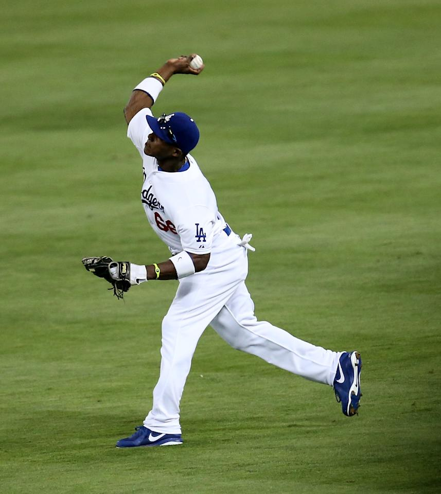 LOS ANGELES, CA - JUNE 08: Right fielder Yasiel Puig #66 of the Los Angeles Dodgers throws to get baserunner Andrelton Simmons of the Atlanta Braves at third base in the fifth inning at Dodger Stadium on June 8, 2013 in Los Angeles, California.  (Photo by Stephen Dunn/Getty Images)